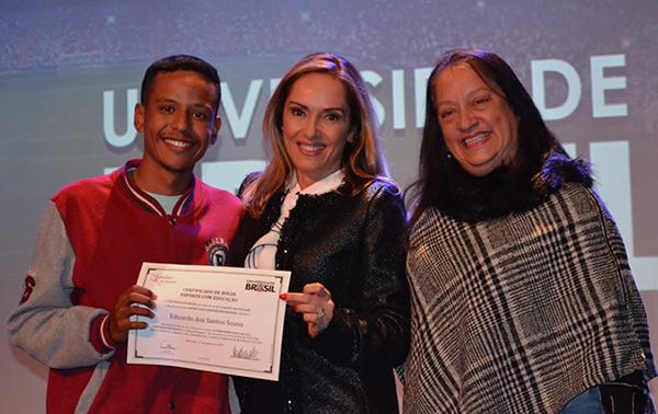 Cláudia Pereira (ao centro) entrega bolsa a aluno contemplado. Foto: Divulgação