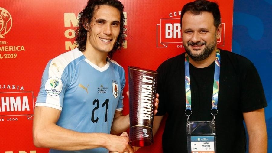 Cavani (e) recebe o prêmio de melhor em campo das mãos de Toninho, dono do Bar do Momo (RJ), após jogo no Maracanã